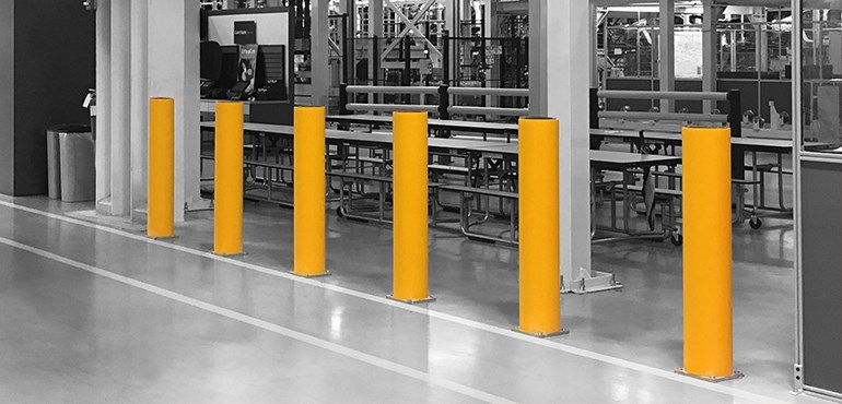 Concrete and Steel Bollards: Polymer bollards protecting machinery in a factory