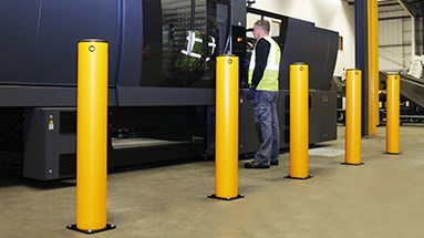Industrial safety bollard protecting machinery in warehouse
