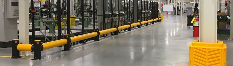 Workplace Safety Barriers: Low level traffic barriers defend a stretch of machinery