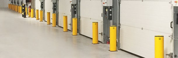Safety bollards protecting industrial doors